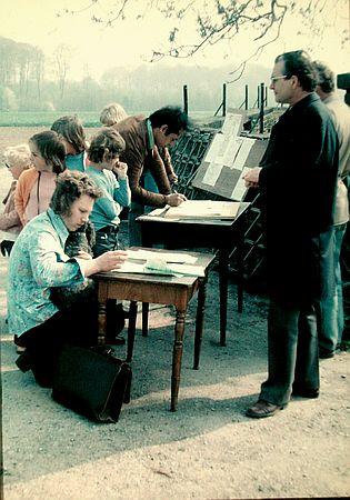 Ein Beispiel für Petitionen aus den 70er Jahren in Deutschland. Mneschn vor Tischen, die zettel unterschreiben