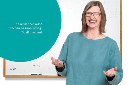"""Porträt Heike Baller vor Whiteboard mit angeschnittenem Kreis (petrolfarben) in dem steht"""" Und wissen Sie war? Recherche kann richtig Spaß machen!"""""""
