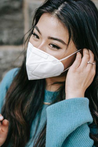 Junge Frau mit langen dunklen Haaren befestigt FFP2-Maske hinterm Ohr